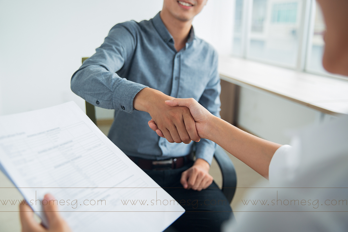 Smiling Asian businessman wearing shirt sitting in office and shaking hand of female partner. Woman holding document